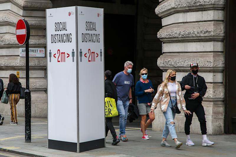 "Members of public wearing face masks walk past a ""Social Distancing"" sign at Regents Street during coronavirus pandemic. It is mandatory to wear face masks while travelling. (Photo by Dinendra Haria / SOPA Images/Sipa USA)"