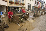 Residents and shopkeepers are trying to clear mud from their homes and move unusable furniture outside in Ahrweiler, western Germany, Saturday, July 17, 2021. Heavy rains caused mudslides and flooding in the western part of Germany. Multiple have died and are missing as severe flooding in Germany and Belgium turned streams and streets into raging, debris-filled torrents that swept away cars and toppled houses. (Thomas Frey/dpa via AP)