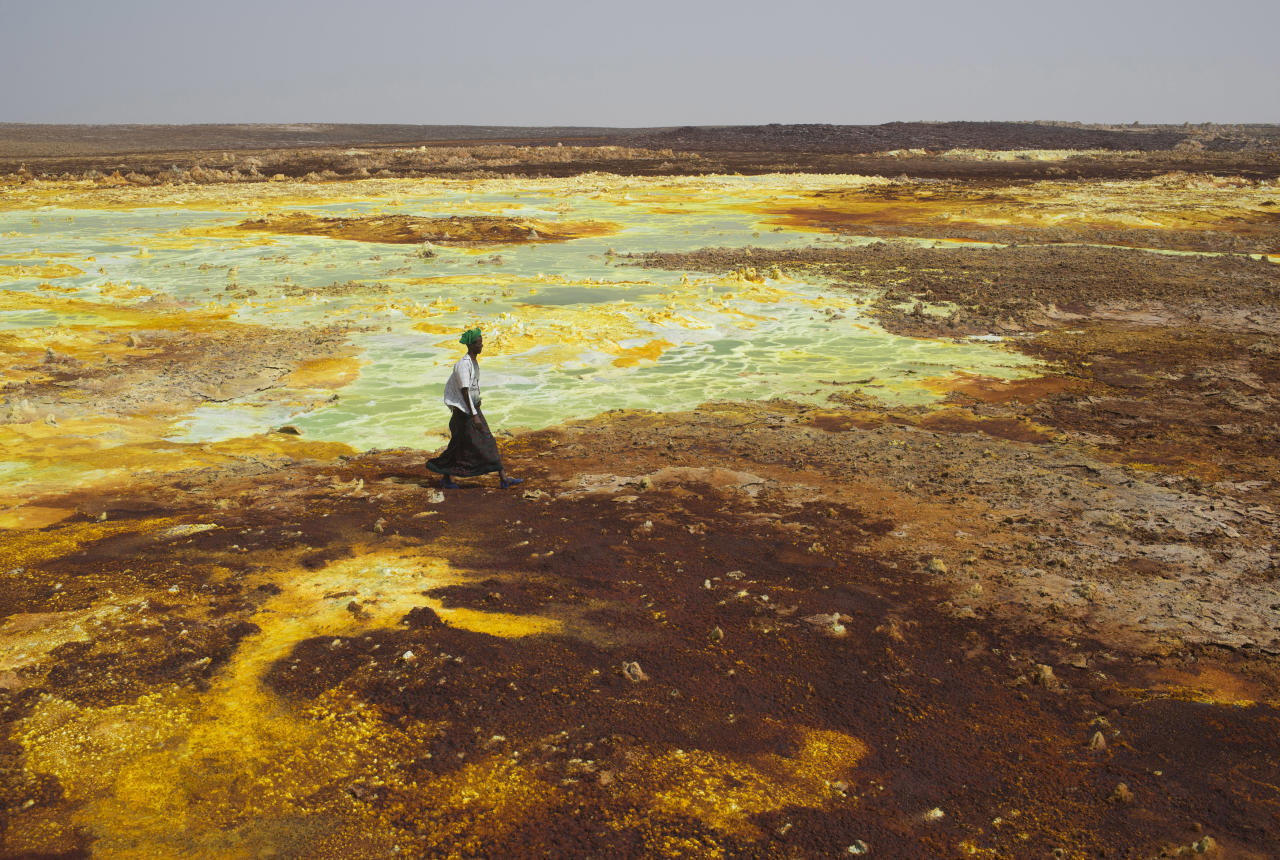 A man walks on sulphur and mineral salt formations near Dallol in the Danakil Depression, northern Ethiopia April 22, 2013. The Danakil Depression in Ethiopia is one of the hottest and harshest environments on earth, with an average annual temperature of 94 degrees Fahrenheit (34.4 Celsius). For centuries, merchants have travelled there with caravans of camels to collect salt from the surface of the vast desert basin. The mineral is extracted and shaped into slabs, then loaded onto the animals before being transported back across the desert so that it can be sold around the country. Picture taken April 22, 2013. REUTERS/Siegfried Modola (ETHIOPIA - Tags: BUSINESS SOCIETY TPX IMAGES OF THE DAY)   ATTENTION EDITORS: PICTURE 2 OF 30 FOR PACKAGE 'ETHIOPIA'S ANCIENT SALT TRAIL' SEARCH 'DANAKIL DEPRESSION' FOR ALL