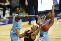 Loyola of Chicago guard Lucas Williamson, center, fights for a rebound with Drake forward Issa Samake, left, and forward Tremell Murphy, right, during the second half of an NCAA college basketball game, Saturday, Feb. 13, 2021, in Des Moines, Iowa. (AP Photo/Charlie Neibergall)