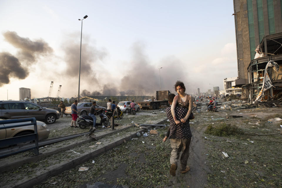 People evacuate the wounded after a massive explosion in Beirut, Lebanon, Tuesday, Aug. 4, 2020. (AP Photo/Hassan Ammar)