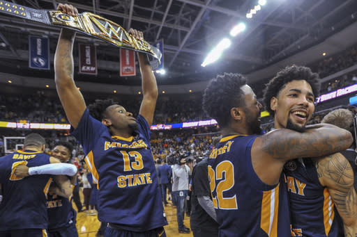 Murray State's Brion Whitley (22) hugs Tevin Brown (10) as Devin Gilmore (13) celebrates behind them the team's win over Belmont in an NCAA college basketball game for the championship of the Ohio Valley Conference men's tournament Saturday, March 9, 2019, in Evansville, Ind. (AP Photo/Daniel R. Patmore)