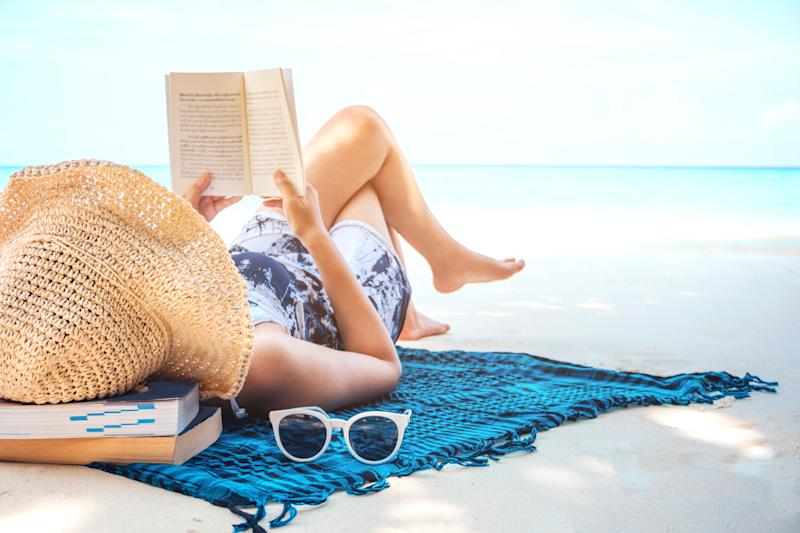 Woman in straw hat at the beach, lying on her back on a beach blanket reading a book. A pair of sunglasses sits by her side.
