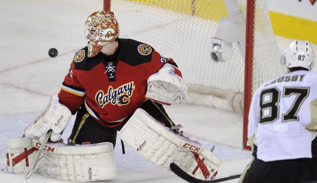 Pittsburgh Penguins' Sidney Crosby, right, puts a shot off the goalpost behind Calgary Flames goalie Reto Berra, from Switzerland, during second-period NHL hockey game action in Calgary, Alberta, Saturday, Jan. 11, 2014. (AP Photo/The Canadian Press, Larry MacDougal)