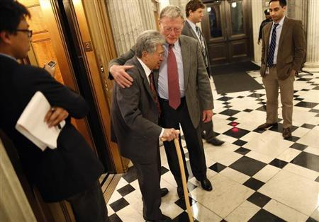 Inhofe hugs Akaka as they cross paths during a senate vote in the early morning hours at the U.S. Capitol in Washington