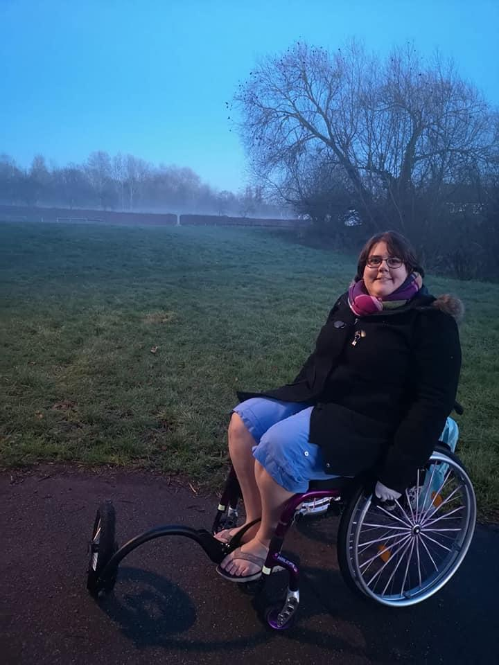Sophie using her wheelchair with an off-road attachment on the front.