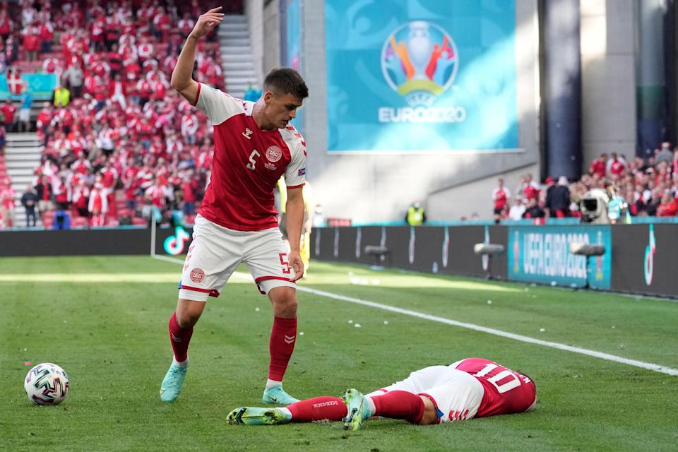 Denmark's Joakim Maehle reacts as teammate Christian Eriksen lies on the pitch after collapsing during the Euro 2020 soccer championship group B match against Finland.