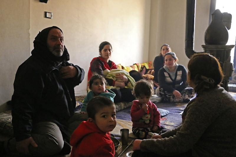 Members of seven displaced Syrian families sit together in an apartment in the Kurdish Syrian town of Afrin on February 1, 2018 (AFP Photo/Ahmad Shafie BILAL)
