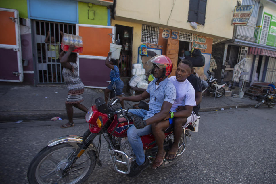 A motorcycle taxi transports Jhon Celestin, deported from the United States two days earlier, to go buy sneakers in Port-au-Prince, Haiti, Friday, Sept. 24, 2021. Before leaving Haiti again, Celestin is planning a trip to the coastal city of Jacmel in southern Haiti to see more relatives, a risky trip because it entails crossing gang-controlled territory. (AP Photo/Joseph Odelyn)