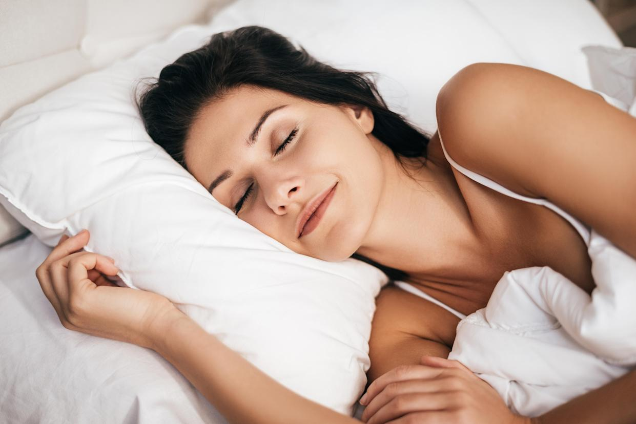 woman smiling during sleeping while lying in the bed at home