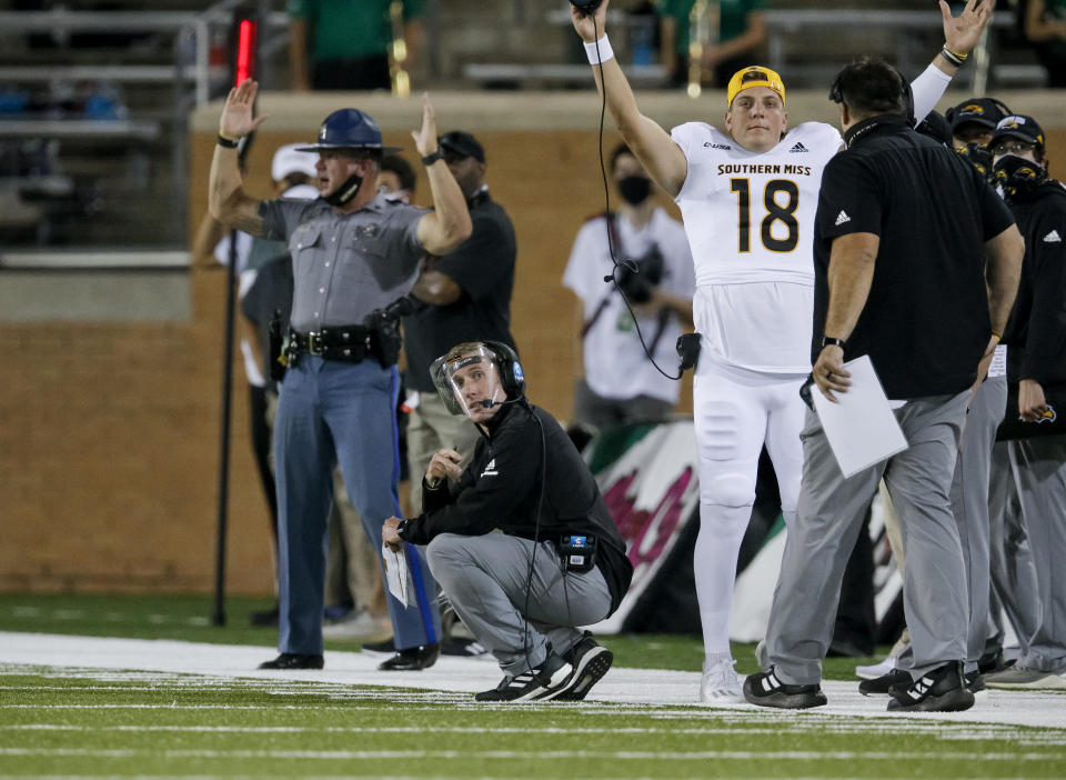 Southern Miss interim head coach Scotty Walden, center, watches a replay of a touchdown scored by running back Darius Maberry (not shown) during the second half of an NCAA college football game against North Texas on Saturday, Oct. 3, 2020, in Denton, Texas. (AP Photo/Brandon Wade)