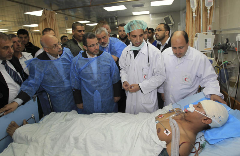 Gaza's Hamas Prime Minister Ismail Haniyeh, center back, and Egyptian Prime Minister Hesham Kandil, center front, visit a man wounded in an Israeli strike, at the hospital in Gaza City, Friday, Nov. 16, 2012. Early Friday, 85 missiles exploded within 45 minutes in Gaza City, sending black pillars of smoke towering above the coastal strip's largest city. The military said it was targeting underground rocket-launching sites. The Israeli offensive has not deterred the militants from firing more than 400 rockets aimed at southern Israel since Wednesday, the military said.(AP Photo/Mahmud Hams, Pool)