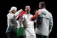 Aron Szilagyi of Hungary, center, celebrates with his staff after winning the gold in the men's individual final Sabre competition at the 2020 Summer Olympics, Saturday, July 24, 2021, in Chiba, Japan. (AP Photo/Andrew Medichini)