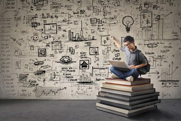 Young Asian boy with black glasses sitting on a stack oversized books, drawing his ideas on the wall behind him while looking at his laptop.
