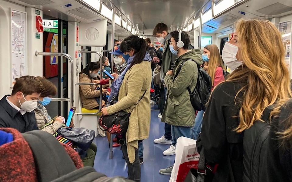 People wear face masks to prevent the spread of COVID-19 as they travel in a subway train, in Milan, Italy - Luca Bruno/AP Photo