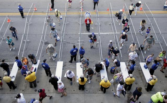 Fans make their way though a security checkpoint as they enter the Indianapolis Motor Speedway before the start of the 98th running of the Indianapolis 500 IndyCar auto race in Indianapolis, Sunday, May 25, 2014. (AP Photo/AJ Mast)