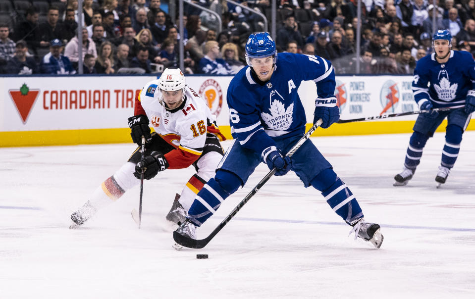TORONTO, ON - JANUARY 16: Mitch Marner #16 of the Toronto Maple Leafs plays the puck against Tobias Rieder #16 of the Calgary Flames during the second period at the Scotiabank Arena on January 16, 2020 in Toronto, Ontario, Canada. (Photo by Kevin Sousa/NHLI via Getty Images)