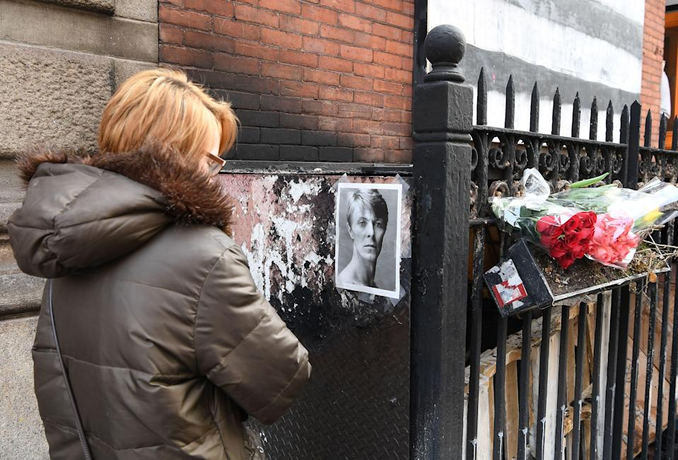 A woman pauses outside David Bowie's SoHo apartment building on 10 January 2017, the first anniversary of the music icon's death. (Angela Weiss/AFP via Getty Images)