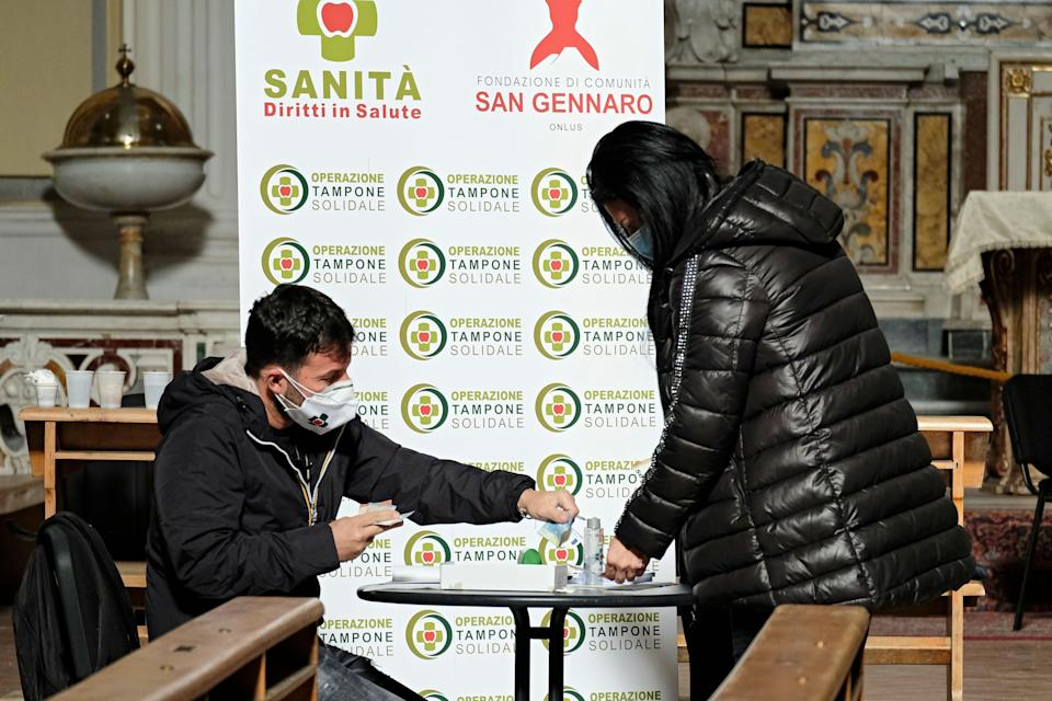 """A local resident donates money during a rapid antigen testing campaign for the Covid-19 disease caused by the novel coronavirus, at the Basilica of """"San Severo fuori le mura"""" in the Rione Sanita district in centre Naples on November 23, 2020. - Associations in Naples offer tests to local residents for 18 euros, or for free in the form of a """"suspended swab test"""", inspired by the tradition of the  """"suspended coffee"""" (""""caffe sospeso"""" in italian). Those who can pay for the test can also buy another one for someone else who cannot afford it. (Photo by Andreas SOLARO / AFP) (Photo by ANDREAS SOLARO/AFP via Getty Images) (Photo: AFP via Getty Images)"""
