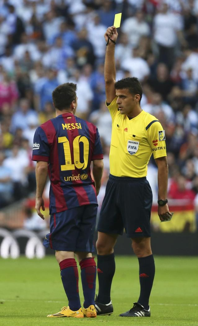 "Barcelona's Lionel Messi (L) is shown a yellow card by referee Gil Manzano during the Spanish first division ""Clasico"" soccer match against Real Madrid at the Santiago Bernabeu stadium in Madrid October 25, 2014. REUTERS/Stringer (SPAIN - Tags: SOCCER SPORT)"