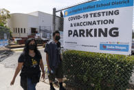 FILE - In this April 15, 2021, file photo, parent Rosa Vargas and her son, 9th grade student Victor Loredo, 14, walk home after getting tested at a Los Angeles Unified School District COVID-19 testing and vaccination site in East Los Angeles. Children are having their noses swabbed or saliva sampled at school to test for the coronavirus in cities. As more children return to school buildings this spring, widely varying approaches have emerged on how and whether to test students and staff members for the virus. (AP Photo/Damian Dovarganes, File)
