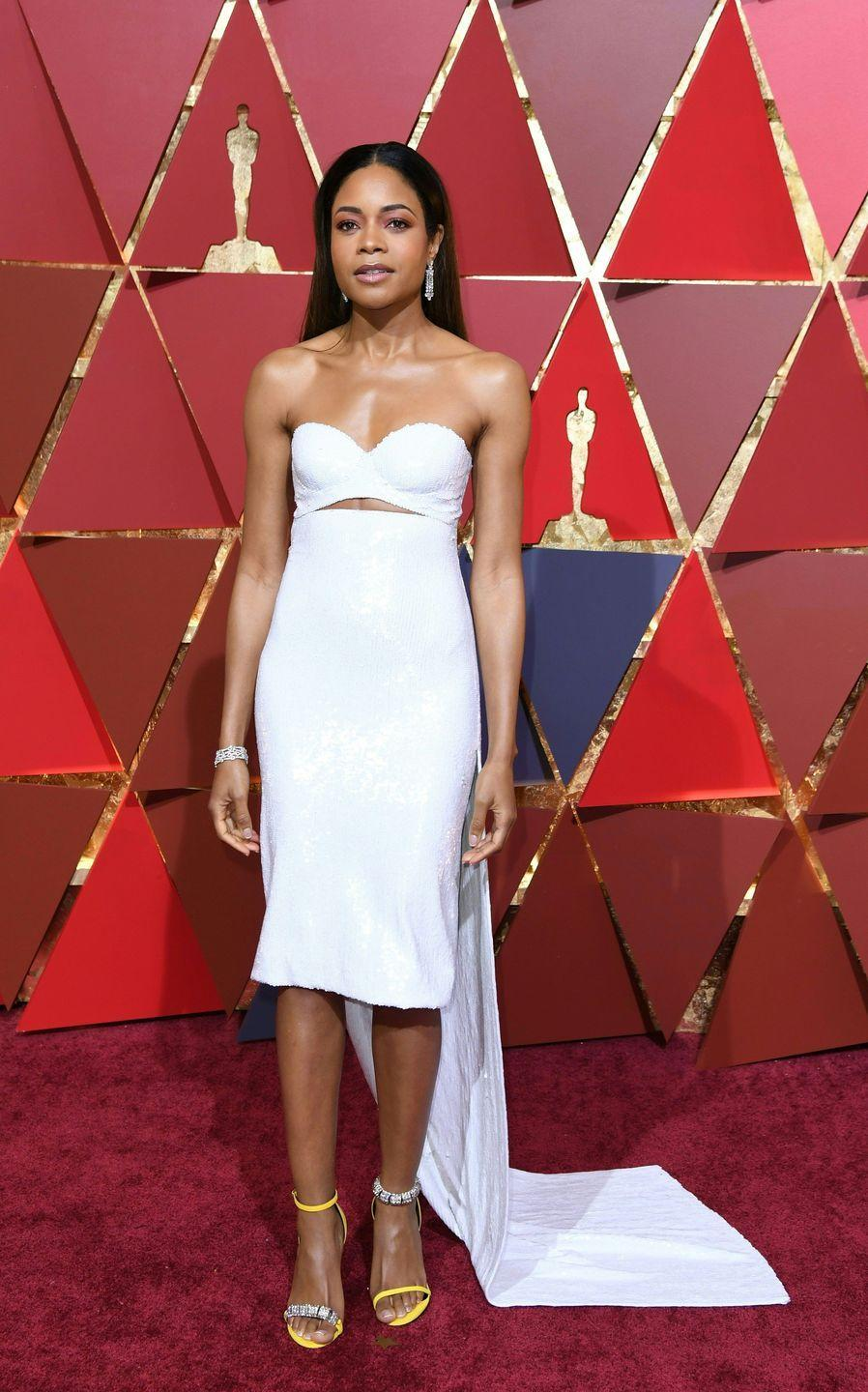 <p>The <em>Moonlight</em> star was nominated for Best Supporting Actress this year, and she didn't play any games on the red carpet. This white sequin Calvin Klein mini was jaw-dropping—especially when paired with her bold yellow heels. </p>