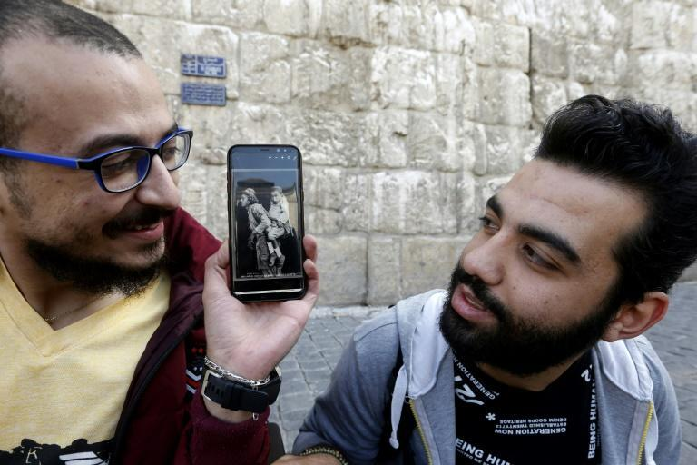 Bader al-Hajjami holds up a black and white photograph that shows two men who also reportedly lived in Damascus - one who was blind and carrying his friend, who could see but not walk