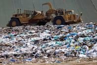 Workers use heavy machinery to move trash and waste at the Frank R. Bowerman landfill in California