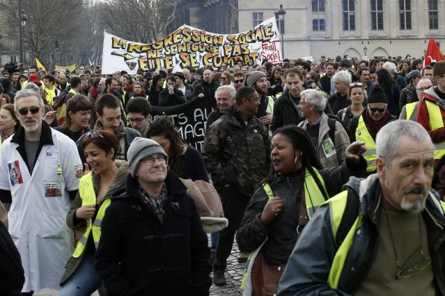 Protesters take part in a rally in Paris, Saturday, March 23, 2019. Yellow vest demonstrators gathered in Paris and other French cities for a 19th round of demonstrations as authorities issued bans on protests in certain areas and enhanced security measures in an effort to avoid a repeat of last week's riots in the capital. (AP Photo/Michel Euler)