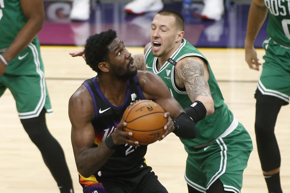 Phoenix Suns center Deandre Ayton, left, looks to shoot as Boston Celtics forward Daniel Theis defends during the first half of an NBA basketball game, Sunday, Feb. 7, 2021, in Phoenix. (AP Photo/Ralph Freso)