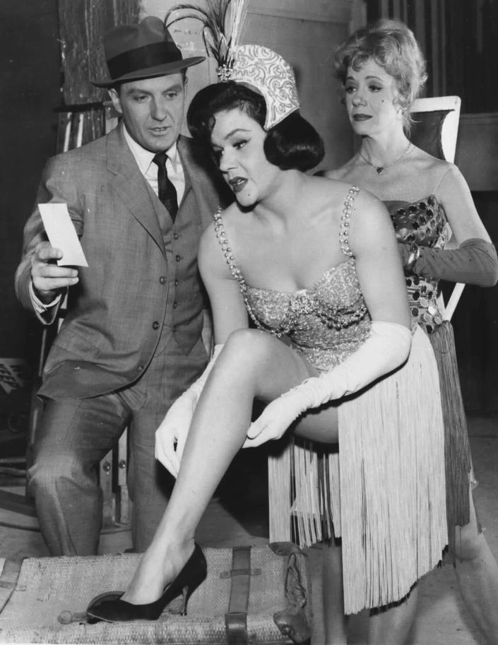 """FILE - In this March 1963 file publicity photo originally released by ABC, actor Robert Stack, portraying Prohibition-era crime fighter Eliot Ness, is shown with Patty Regan, center, and Sherry O'Neil, who play chorus girls in a scene from the ABC television show """"the Untouchables."""" Illinois' two U.S. senators have proposed naming the Bureau of Alcohol, Tobacco, Firearms and Explosives in Washington after Ness, but a prominent Chicago alderman and others point to evidence that Ness' role in the demise of Chicago mobster Al Capone was as mythical as Mrs. O'Leary's cow starting the Great Chicago Fire and are trying to convince the senators to drop the whole thing. (AP Photo/ABC, File)"""