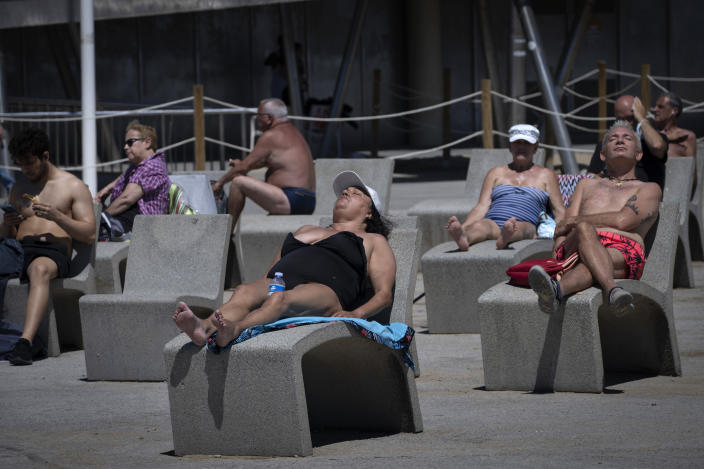 FILE - In this Tuesday, June 8, 2021 file photo, people sunbathe near the beach in Barcelona, Spain. Europe is opening up to Americans and other visitors after more than a year of COVID-induced restrictions. European governments hope to lure back tourists - and their dollars - back to the continent's trattorias, vistas and cultural treasures. (AP Photo/Emilio Morenatti, File)