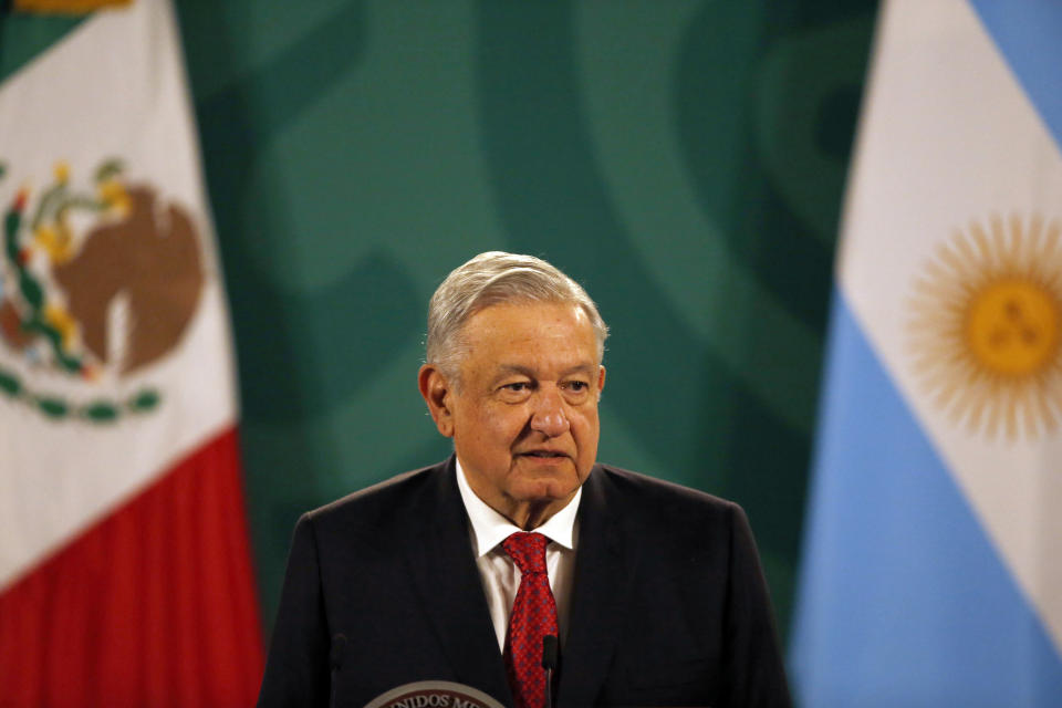 Mexican President Andrés Manuel López Obrador gives his daily, morning press conference at the National Palace in Mexico City, Tuesday, Feb. 23, 2021, with an Argentine flag in the background, right, as Argentine President Alberto Fernandez attends the event. (AP Photo/Marco Ugarte)