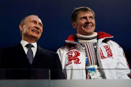FILE PHOTO: Russian President Vladimir Putin (L) laughs with Russia's gold medallist bobsleigh athlete Alexander Zubkov during the closing ceremony for the 2014 Sochi Winter Olympics, February 23, 2014. REUTERS/Phil Noble/File Photo