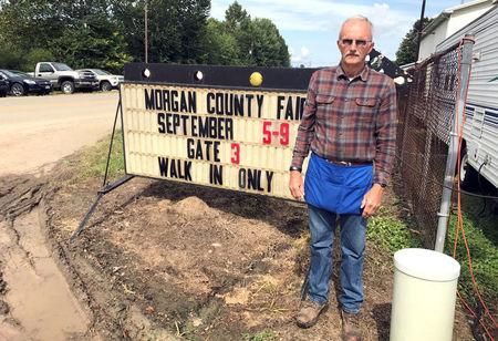 John Wilson, 70, stands next to a sign at the Morgan County Fair in McConnelsville, Ohio, U.S., September 6, 2017. Photo taken September 6, 2017. REUTERS/Tim Reid/Files