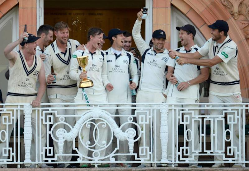 Nick Gubbins holds the trophy on the dressing room balcony after Middlesex win the 2016 County Championship