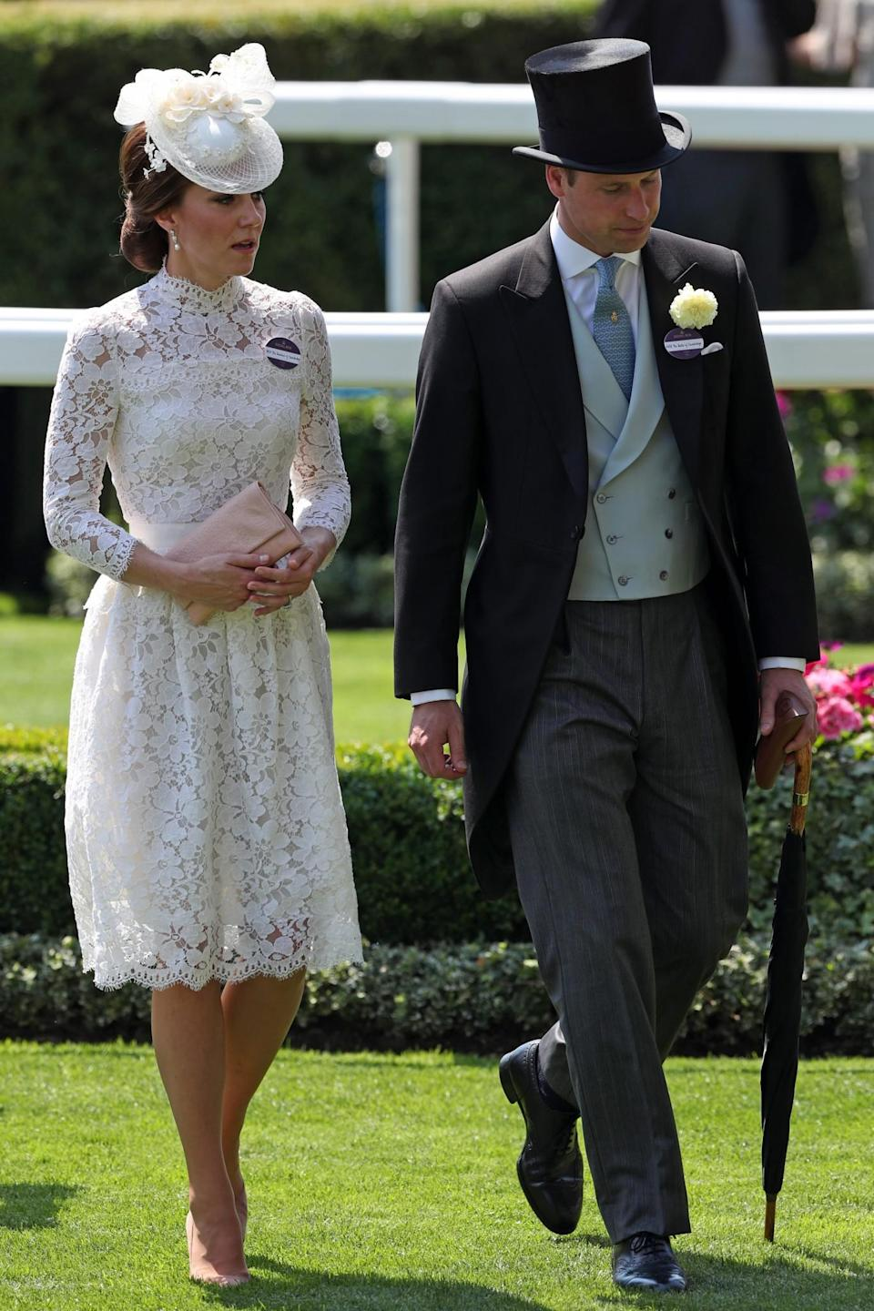 <p>Kate and William arrived at the 2017 race event in a very similar look to last year. The Duchess donned a white lacy dress by Alexander McQueen with a pearl-embroidered hat while William went for a black-and-grey morning suit.<br><i>[Photo: PA]</i> </p>