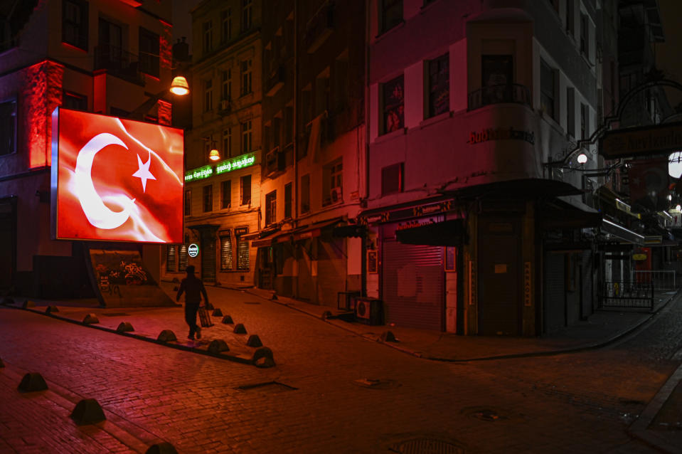 FILE - In this Wednesday, Nov. 25, 2020, file photo, a man walks during a night curfew, due to the virus pandemic, in Istanbul. When Turkey changed the way it reports daily COVID-19 infections, it confirmed what medical groups and opposition parties have long suspected — that the country is faced with an alarming surge of cases that is fast exhausting the Turkish health system. The official daily COVID-19 deaths have also steadily risen to record numbers in a reversal of fortune for the country that had been praised for managing to keep fatalities low. With the new data, the country jumped from being one of the least-affected countries in Europe to one of the worst-hit.(AP Photo, File)