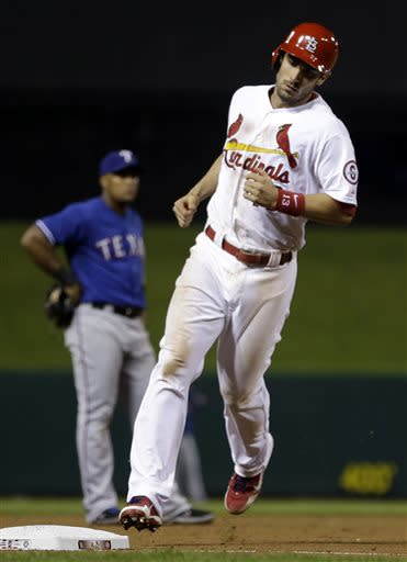 St. Louis Cardinals' Matt Carpenter, right, rounds the bases after hitting a solo home run as Texas Rangers third baseman Adrian Beltre, left, watches during the sixth inning of a baseball game on Sunday, June 23, 2013, in St. Louis. (AP Photo/Jeff Roberson)