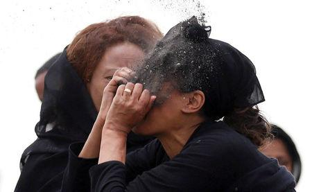 A relative puts soil on her face as she mourns at the scene of the Ethiopian Airlines Flight ET 302 plane crash, near the town Bishoftu