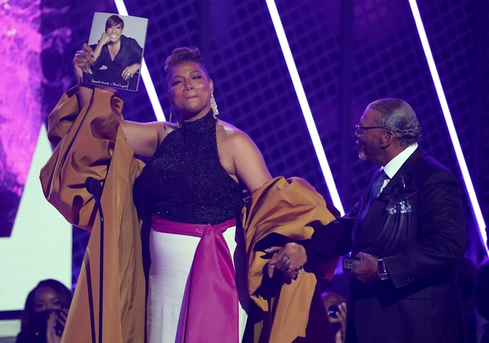 Queen Latifah, winner of the lifetime achievement award, holds a photo of her late mother Rita Owens as she walks with her father Lancelot Owens, Sr.
