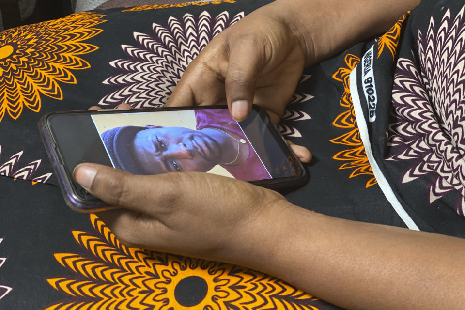 FILE - In this Friday, March 5, 2021 file photo, Anifa holds her phone displaying a photo of former World Health Organization doctor Boubacar Diallo of Canada, during an interview in the eastern Congo town of Goma. A panel commissioned by the World Health Organization on Tuesday Sept, 28, 2021 identified more than 80 alleged cases of sex abuse during the U.N. health agency's response to an Ebola outbreak in Congo, including allegations implicating 20 WHO staff members. (AP Photo/Kudra Maliro, File)