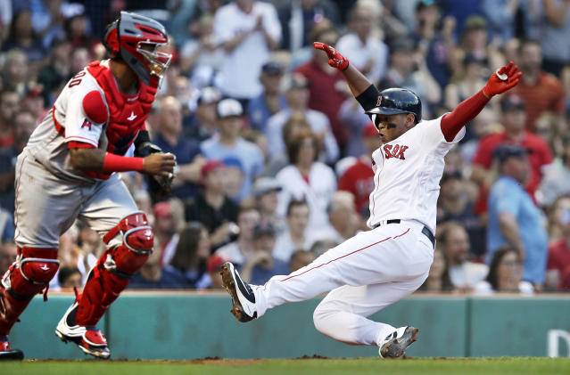 Boston Red Sox's Rafael Devers scores on a double by Jackie Bradley Jr. during the second inning of a baseball game against the Los Angeles Angels at Fenway Park in Boston, Tuesday, June 26, 2018. At left is Angels catcher Martin Maldonado. (AP Photo/Charles Krupa)