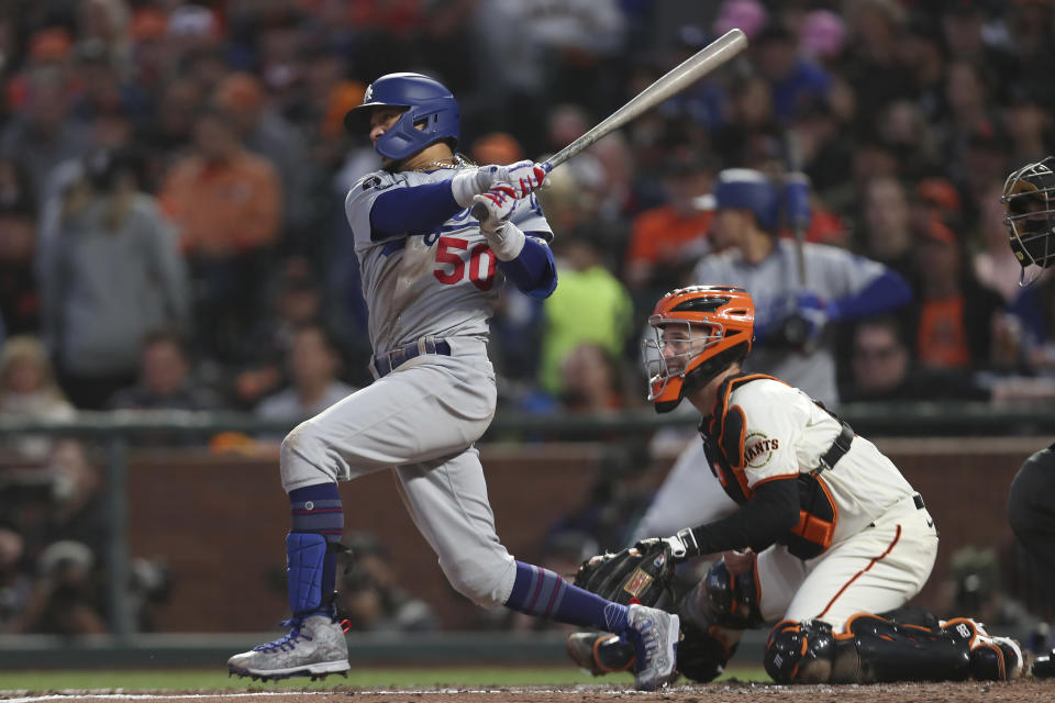 Los Angeles Dodgers' Mookie Betts, left, hits an RBI-single in front of San Francisco Giants catcher Buster Posey during the second inning of Game 2 of a baseball National League Division Series Saturday, Oct. 9, 2021, in San Francisco. (AP Photo/Jed Jacobsohn)