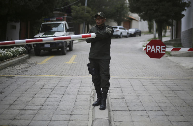 A police officer stands at the entrance leading to the residence of Mexico's ambassador to help make sure nine former officials from the government of deposed Bolivian President Evo Morales, who have taken refuge inside, do not leave the country, in La Paz, Bolivia, Monday, Dec. 30, 2019. Bolivia's interim government is expelling the top Mexican and Spanish diplomats in the country over an alleged attempt by members of Bolivia's former government to leave refuge in the Mexican embassy with Spanish help and flee the country. (AP Photo/Luis Gandarillas)