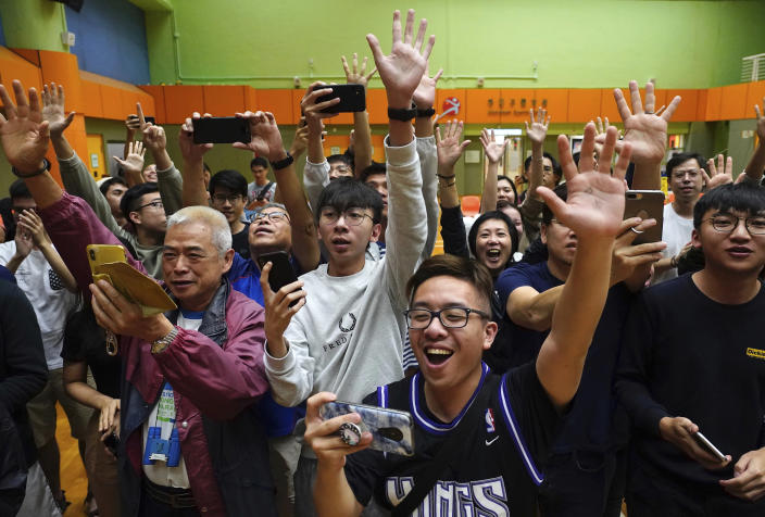 Supporters of pro-democracy candidate Angus Wong celebrate after he won in district council elections in Hong Kong, early Monday, Nov. 25, 2019. Vote counting was underway in Hong Kong early Monday after a massive turnout in district council elections seen as a barometer of public support for pro-democracy protests that have rocked the semi-autonomous Chinese territory for more than five months. (AP Photo/Vincent Yu)