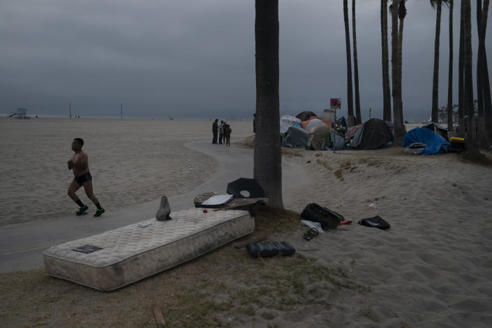A man jogs past a mattress as several homeless people mingle next to their encampment set up along the boardwalk in the Venice neighborhood of Los Angeles, Tuesday, June 29, 2021. The proliferation of homeless encampments on Venice Beach has sparked an outcry from residents and created a political spat among Los Angeles leaders. (AP Photo/Jae C. Hong)