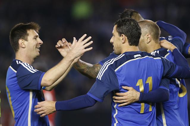 Argentina's Maximiliano Rodriguez, center, celebrates his goal against Trinidad and Tobago with teammate Lionel Messi, left, during an international friendly soccer match in Buenos Aires, Argentina, Wednesday, June 4, 2014. (AP Photo/Victor R. Caivano)