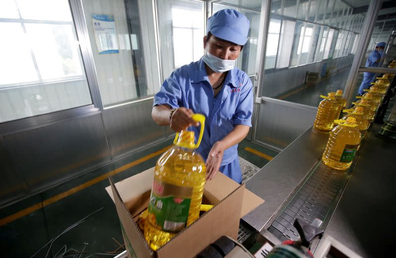 FILE PHOTO: A worker packs bottles of soybean oil made from imported U.S. soybeans at the plant of Liangyou Industry and Trade Co., Ltd in Qufu