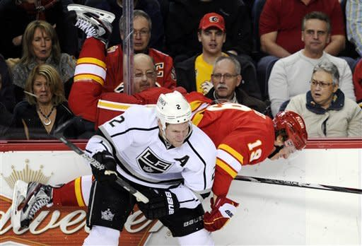 Los Angeles Kings' Matt Greene (2) checks Calgary Flames' Blair Jones (19) into the boards during the first period of an NHL hockey game in Calgary, Alberta, Saturday, Jan. 14, 2012. (AP Photo/The Canadian Press, Larry MacDougal)